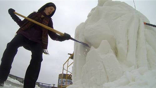 CORRECTS SPELLING OF LAKE GENEVA - In this photo taken Jan. 29, 2015, in Lake Geneva, Wis., sculptor Jenna Odhner, from the New Hampshire team, carves a nine-foot high block of snow during the U.S. National Snow Sculpting Championship. (AP Photo/Carrie Antlfinger)