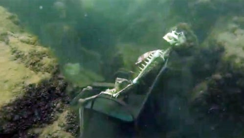 In this frame from video provided by the La Paz Sheriffs' Office, fake skeletons are strategically placed to appear as if they were sitting together with their lawn chairs bound to large rocks in the Colorado River near the Arizona and California border. A man snorkeling came across the two fake skeletons sitting in lawn chairs about 40 feet underwater and reported the skeletons to the La Paz County Sheriff's Office on Monday, May 4, 2015, launching a hunt for what authorities believed could be real bodies.