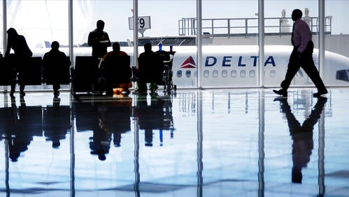 In this October 2016, photo, a Delta Air Lines jet sits at a gate at Hartsfield-Jackson Atlanta International Airport, in Atlanta. Delta is giving airport employees permission to offer passengers up to almost $10,000 in compensation to give up their seats on overbooked flights.