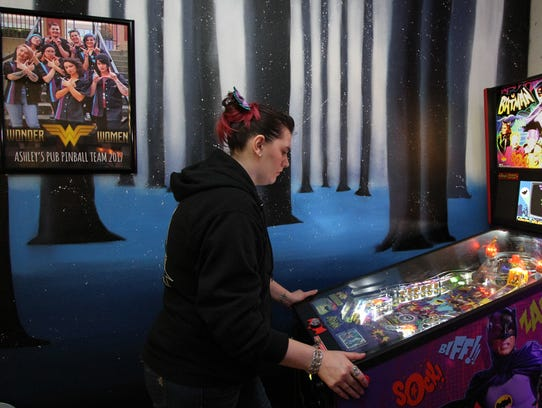Allyson Adams takes her turn at the Batman machine during a competition against the Slippery Pig team at Ashley's Pub. Adams' team, Ashley's Avengers, pictured at left, is the home team for the pub.