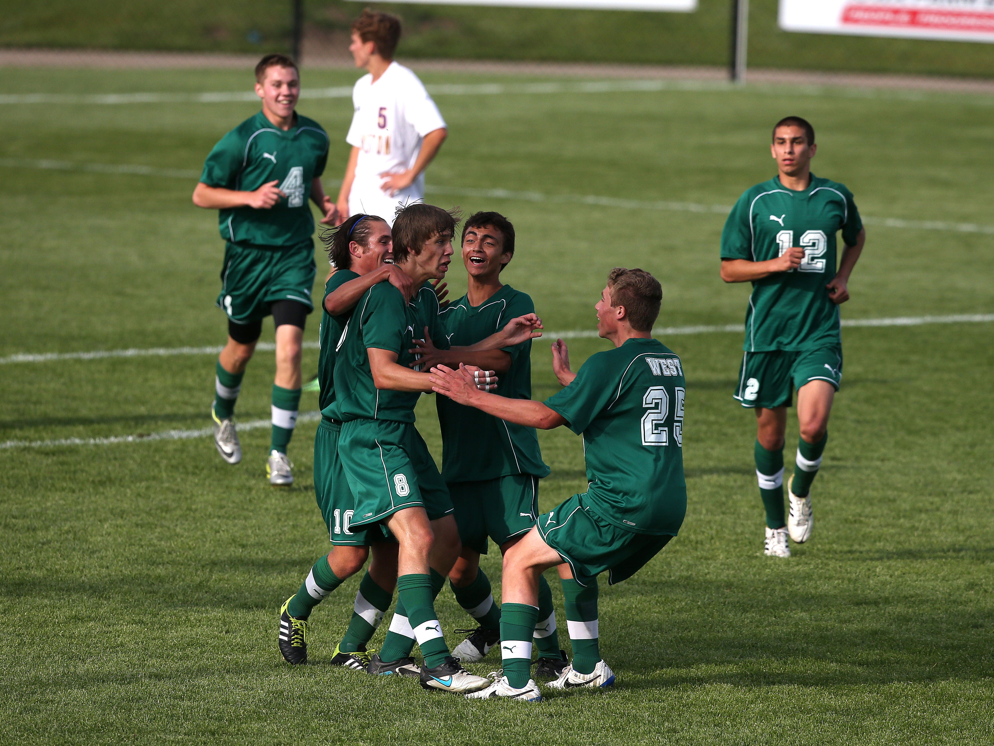 Members of the Iowa City West soccer team mob Jack Olson after he scored a goal to help the Trojans to a 1-0 win over Johnston in last year's Class 3-A final.