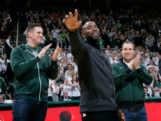 Former Michigan State player Mateen Cleaves, center, flanked by Jason Andreas, left, and Mat Ishbia, right, waves as he is introduced with Michigan State's 2000 national championship team during halftime of Michigan State-Florida game, Saturday in East Lansing.