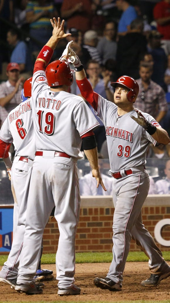 Cincinnati Reds' Devin Mesoraco (39) celebrates his grand slam off Chicago Cubs relief pitcher Hector Rondon with Billy Hamilton (6) and Joey Votto, during the ninth inning of a baseball game Monday.