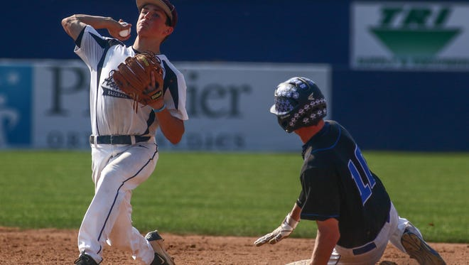 Caravel second baseman Kevin Keister (left) tries to turn a double play during the Buccaneers' 11-1 semifinal win over Middletown on Saturday at Frawley Stadium.