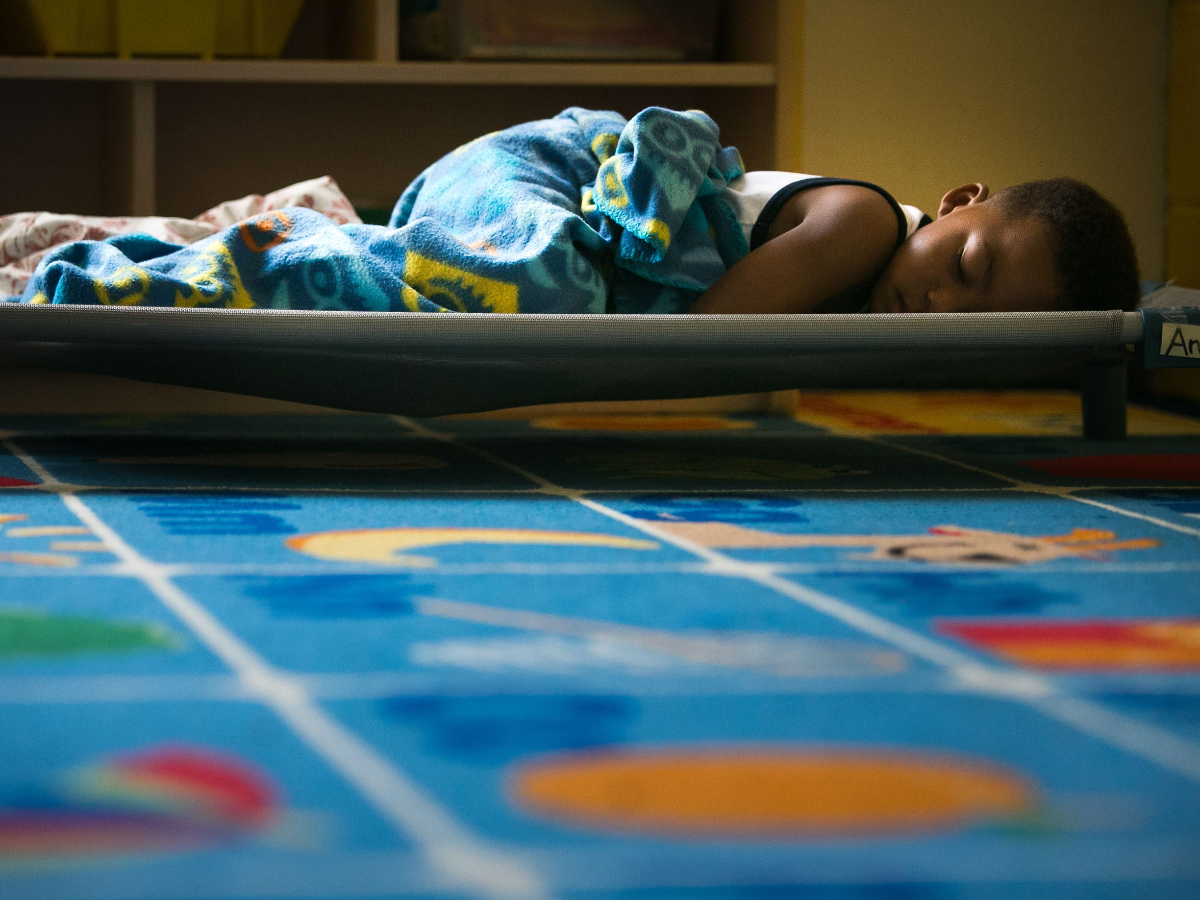 Anmad Helm-Brown, 4, sleeps during nap time in the Early Learning Center at Kingswood Community Center in Wilmington which has been struggling to do such things as find money to not only run its programs, but also find money to pay bills and replace their leaking roof located just outside the hallway of his classroom.