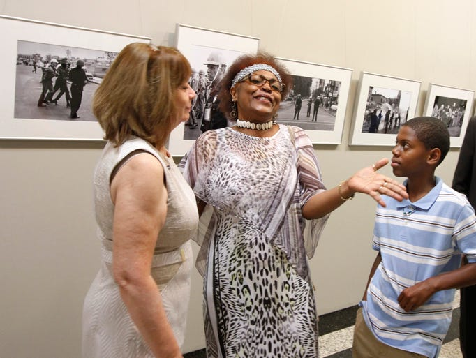 MaryAnn Brown, Rochester, center, talks about seeing a photo of her grandfather Grant Hill hanging in the exhibit for the first time to grandson Kevon Weech, 11, Winchester, VA, and Christine Christopher, Director Bureau of Communications & Special Events for the City of Rochester, left.
