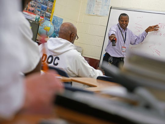 Rodney Callender, a teacher at James T. Vaughn Correctional Center, teaches math to a group of inmates at the prison's educational center.