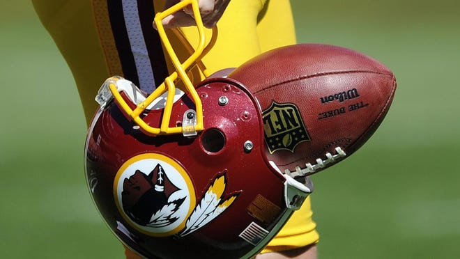 "In this Sept. 23, 2012, file photo, Washington Redskins punter Sav Rocca carries a football in his helmet before an NFL football game against the Cincinnati Bengals in Landover, Md. Washington owner Daniel Snyder plans to announce the retirement of the ""Redskins"" nickname and reveal a new team name Monday morning, a person with knowledge of the situation confirmed to USA TODAY Sports."