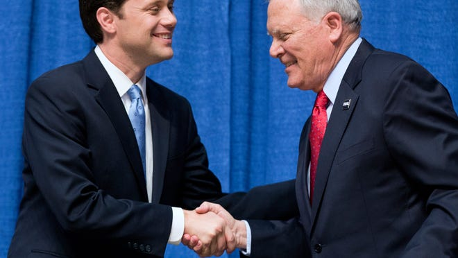 """FILE - IN this Oct. 7, 2014, photo, Gov. Nathan Deal, Georgia Republican candidate for governor, right, shakes hands with Democratic candidate Jason Carter, left, following a debate in Perry, Ga. Candidates everywhere this midterm election season are struggling for ways to frame the state of the economy, ranked by voters as the most important issue. The result is a blame game that cuts in multiple directions depending on the contest _ even, in one case, within the same state. Deal stood on stage while his Democratic challenger _ Carterís grandson _ sharply blamed the governor for Georgiaís 8.1 percent unemployment rate, which in August was the nationís highest. """"You have watched this economy in Georgia leave the middle class behind,"""" said Jason Carter, a state senator.  (AP Photo/David Goldman) ORG XMIT: WX103"""