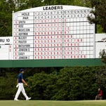 Jordan Spieth walks past a leaderboard during the final round of the 2015 Masters at Augusta National Golf Club.