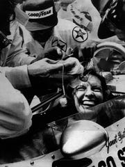Janet Guthrie is all smiles as her pit crew swarms