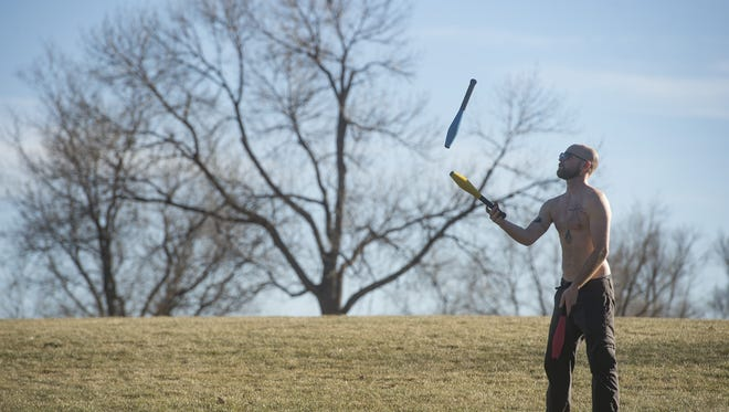 Daniel Nelson juggles on the grass as temperatures hover in the high 50s in City Park on Tuesday, December 12, 2017.