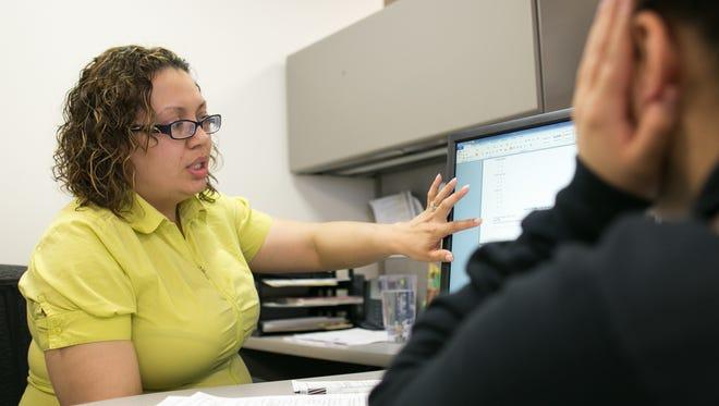 Yolanda Cubero helps a client improve her résumé at RochesterWorks! in Rochester on Thursday, April 16, 2015.