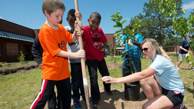 In this 2014 photo, a group of O.J. Semmes Elementary School students help Earth Day volunteer Chancey Bubien, right, plant a fruit tree on the school's campus Tuesday morning April 22, 2014.