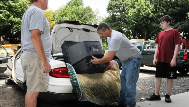 In this 2011 photo, Glen Ridge resident Matt Carey, left,  brings in an outdated television set for recycling at the Glen Ridge Department of Public Works. He is assisted by Public Works Supervisor Bill Bartlett, center, and Andrew Waugh, right.