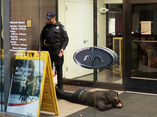 University of Michigan Police Department Patrol Officer Tony Ricco talks with a homeless person as an intoxicated male lies on the ground inside the entrance to a bank in downtown Ann Arbor while patrolling the area in the early morning on Friday, Oct. 16, 2015.