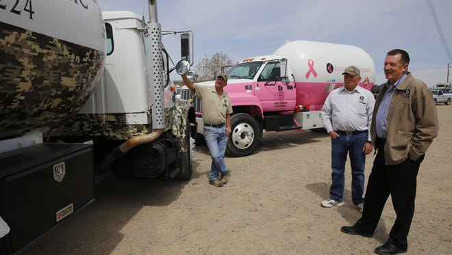 Mike Helms, left, general manager for Arrowhead Propane, and company owners Jake Cluff and Kent Misemer, talk about the pink and camouflage-colored propane trucks that raise money for local charity groups, at their business earlier this month.