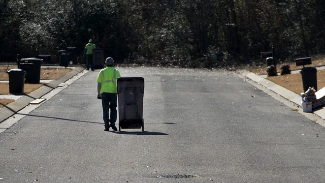Waste Management employees L.T. McNairy (near) and Darius Jones (far) roll garbage bins down one of the streets on their route Tuesday. The bins are used to collect the garbage that sits on the curb or in the backyard of a home in Jackson.