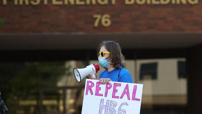 March organizer Matthew Marton of Our Revolution Akron leads a group of around 20 people in chanting outside the FirstEnergy Building during a rally to repeal House Bill 6, Saturday, Aug. 22, 2020, in Akron, Ohio.