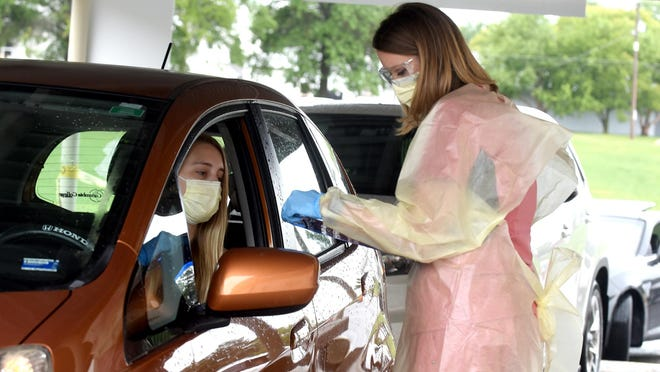 Janna Schremmer, right, a laboratory outreach supervisor, gets information from Megan Castleberry, a Boone Hospital Center phlebotomist, on Tuesday at the hospital's drive-through testing site.