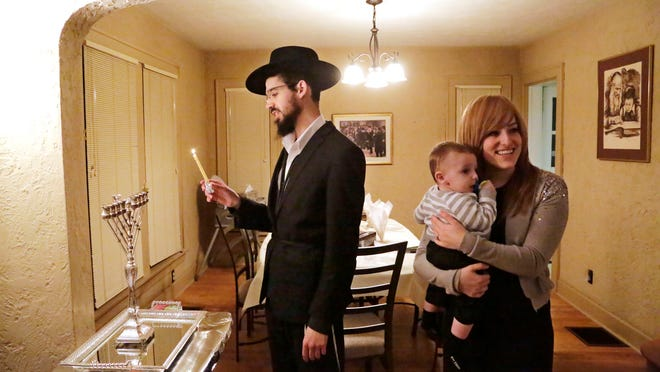 Rabbi Levi Tiechtel says a prayer before lighting the menorah on the first night of Hanukkah Tuesday in his West Lafayette home, which also serves as the new Chabad at Purdue center. At right is Tiechtel's wife, Adina, and their 8-month-old son Mendel.