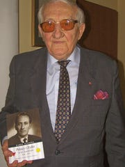 Polish Auschwitz survivor Karol Tendera holds the book he wrote about his experiences.
