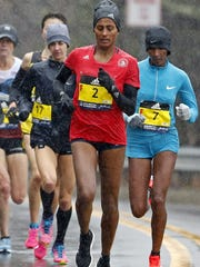 Molly Huddle, left, with bib No. 17, competes in the Boston Marathon along with Buzunesh Deba (2) and Mamitua Daska on Monday.