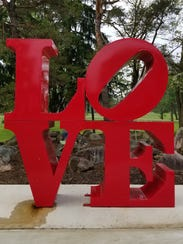 """A """"LOVE"""" sculpture sits at the corner of Grand and"""