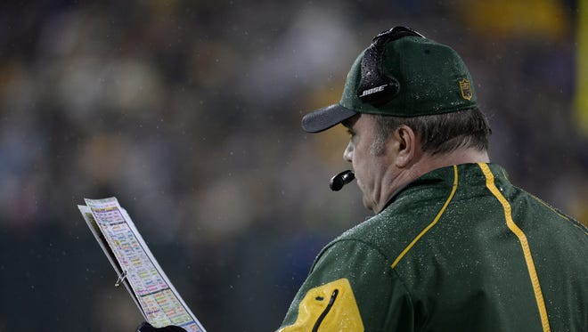 Green Bay Packers coach Mike McCarthy glances as the playbook during a November 2015 game against the Dallas Cowboys.