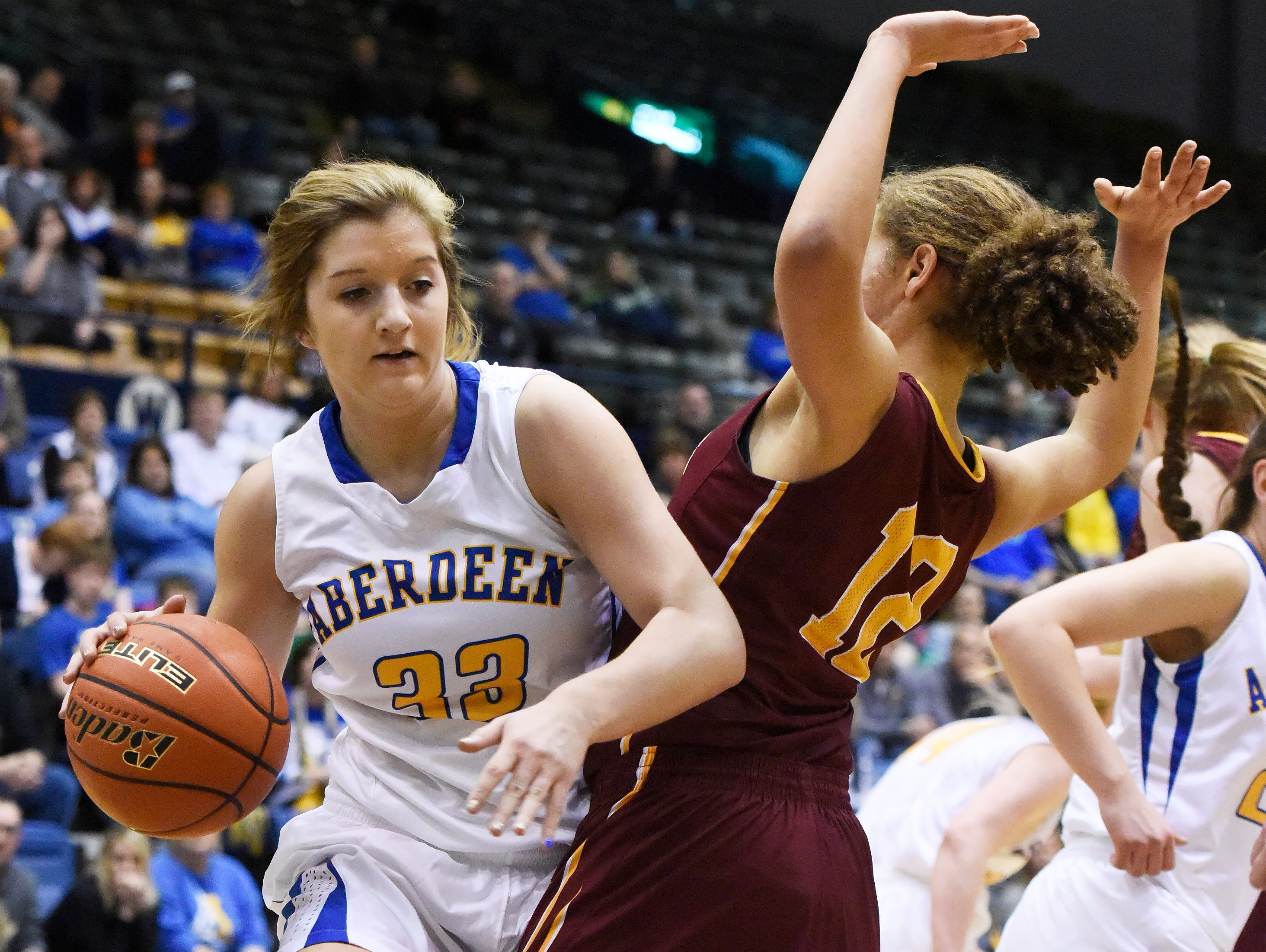 Aberdeen Central's Paiton Burckhard (33) pushes past Roosevelt's Kira Ward (12) with the ball in a state girls class AA basketball quarterfinal March 17.