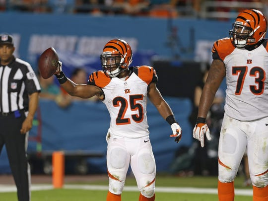 Bengals running back Gio Bernard (25) holds the football after scoring a touchdown against the Miami Dolphins' during the third quarter of their game played at Sun Life Stadium in Miami on Thurs., October 31, 2013.