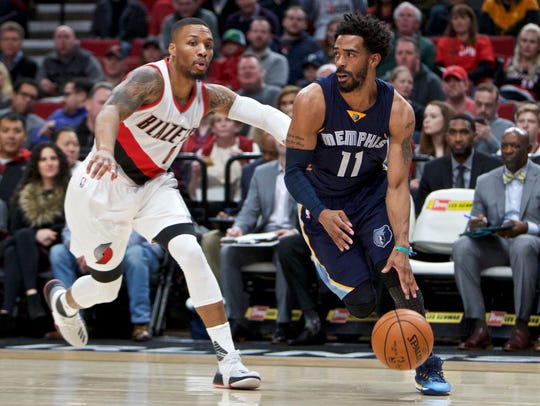 Memphis Grizzlies guard Mike Conley, right, dribbles