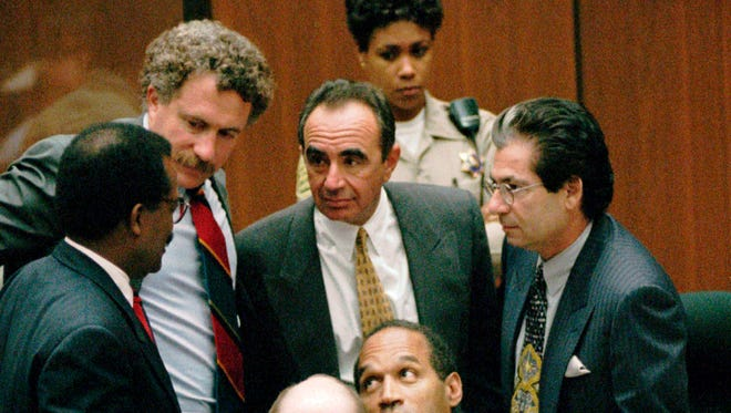 In this September 1995 file image, O.J. Simpson is surrounded by his defense attorneys at the close of defense arguments in Los Angeles.
