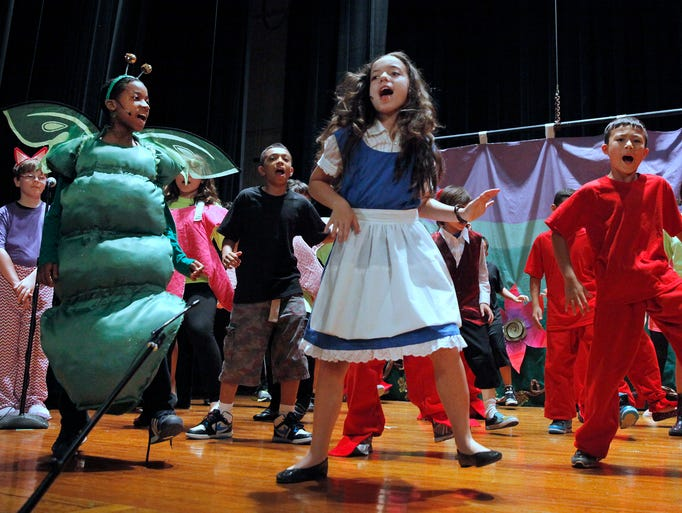 """Students from School 25 and Durand Eastman Intermediate School perform during the dress rehearsal of """"Alice in Wonderland"""" at Durand. In front at left as the """"caterpillar"""" is Durand's Shalimar Stenson and at right as """"small Alice"""" is Durand's Nora Fitzsimmons."""