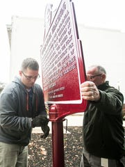 From left, Judicial Center Assistant Maintenance Supervisor Scott Lewis tightens a screw, as Facilities Manager Vada Fink holds the sign, while reinstalling the First National Thanksgiving marker, near 21 E. Market Street Tuesday, Nov. 1, 2016, in York City. An anonymous donor had the York City First National Thanksgiving marker sanded and repainted. Amanda J. Cain photo