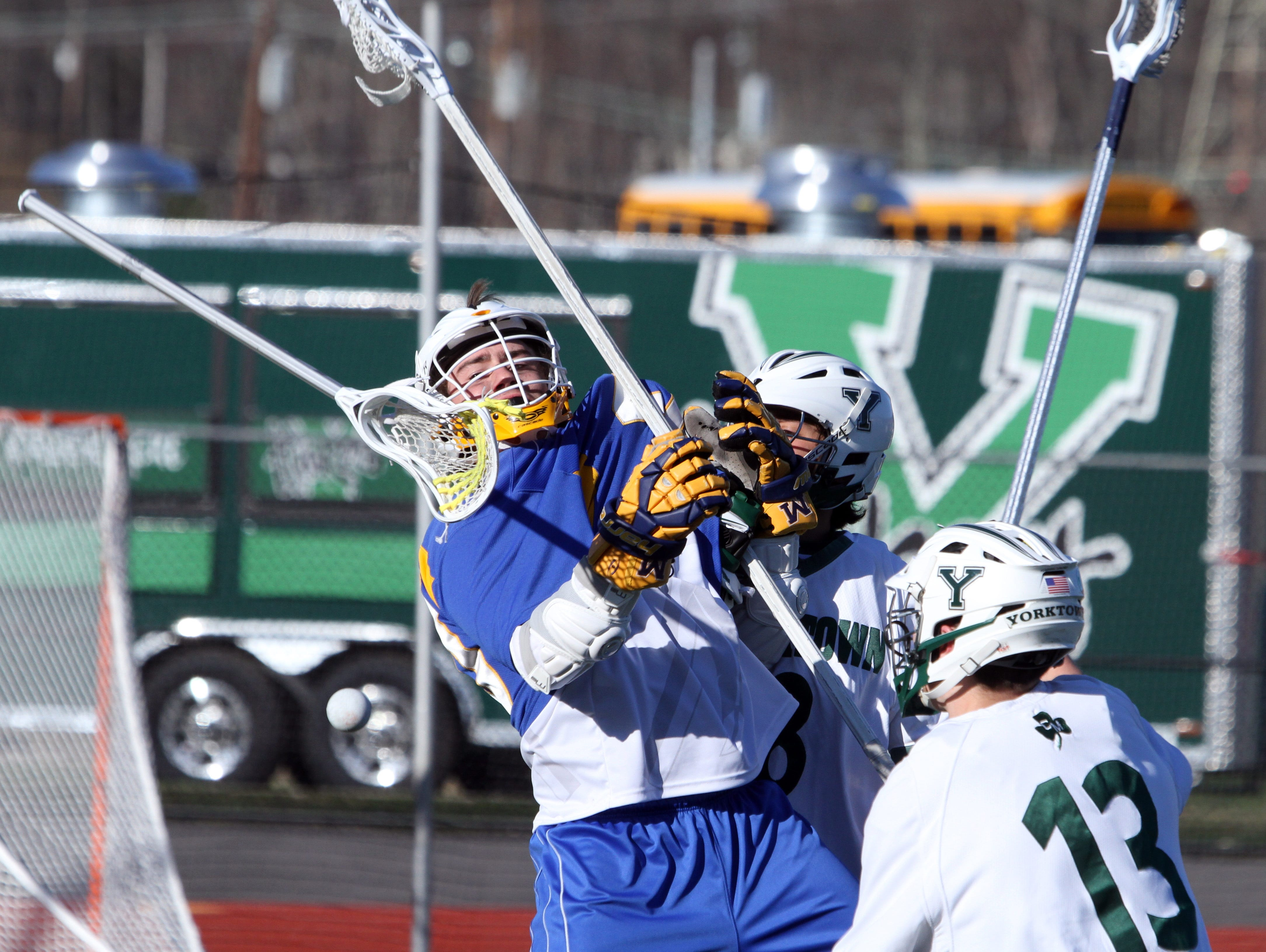 Mahopac's Tom Murray loses his stick while being pressured by Yorktown's Joseph Brancato and Jose Boyer during a varsity lacrosse game at Yorktown High School March 29, 2016. Yorktown defeated Mahopac 15-8.