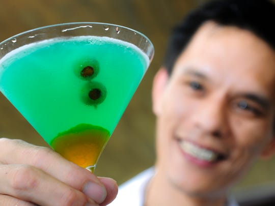 Two skewered stuffed-olives gaze out from the eerie green glow of a Witch's Glare cocktail, prepared by bartender Jun Navarro, while poolside at the Tasi Grill in the Dusit Thani Guam Resort in Tumon on Oct. 26.