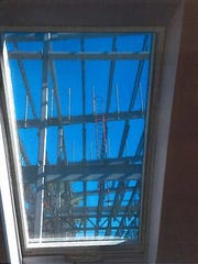 This photograph shows the steel structure of the Conesus Inn as seen through the skylight of a neighboring property.