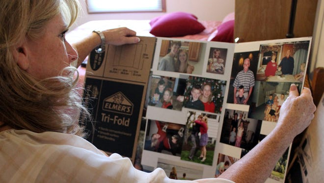 Trudy Reeb holds a poster board with photos of her son, Ryan.