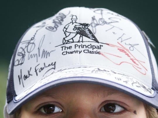 Nicholas Walker looks for another golfer to sign his hat, which is already crowded with signatures at the 2012 Principal Charity Classic at Glen Oaks Country Club, West Des Moines.