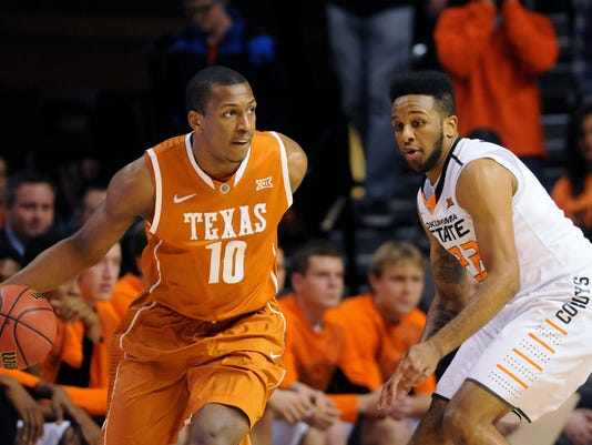 Texas forward Jonathan Holmes, left, looks for an opening to get past Oklahoma State forward Jeff Newberry during the first half of an NCAA college basketball game in Stillwater, Okla., Saturday, Jan. 10, 2015. Oklahoma State defeated Texas 69-58. (AP Photo/Brody Schmidt)