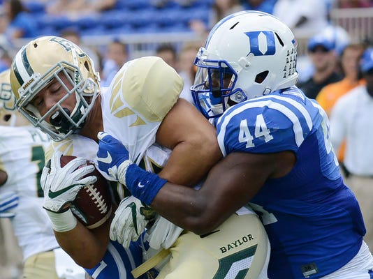 FILE - In this Sept. 16, 2017, file photo, Baylor's Dru Dixon battles Duke's Joe Giles-Harris (44) for yardage during an NCAA college football game, in Durham, N.C. Giles-Harris was selected to the AP All-Conference ACC team announced Tuesday, Dec. 5, 2017. (Bernard Thomas/The Herald-Sun via AP, File)