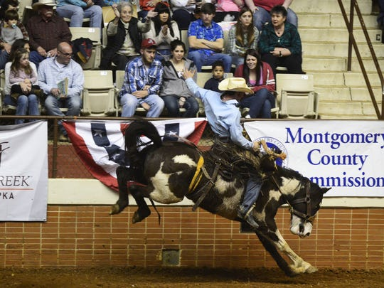 Spectators watch as Shane Kuhn competes in the Saddle Bronc competition during the SLE Rodeo at Garrett Coliseum in Montgomery, Ala. on Friday March 14, 2014.