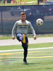 Michigan fullback Joe Beneducci kicks a soccer ball as the U-M football team and AS Roma work out on Monday, July 17, 2017, in Ann Arbor.