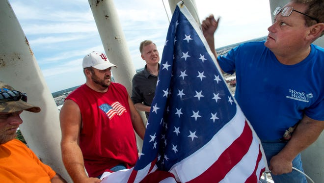 A team of volunteer flag raisers, from left, Randy Seibert, Denny Elliott, Neil Woods and Steve Woods, attach Old Glory, a 4' x 6' cotton version, to a newly repaired halyard in the cupola of the Old Vanderburgh County Courthouse in Downtown Evansville Friday morning. Since the last halyard broke, a planned maintenance system has been created to replace the cable-lined rope every two years.