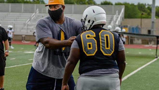 Battle head football coach Atiyyah Ellison, left, wears a mask as he gives instructions to Victor Tyson (60) and other players during preseason practice Tuesday at Battle High School.