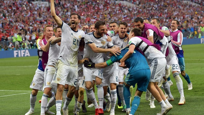 Members of Russia's World Cup team celebrate after beating Spain Sunday to advance to the quarterfinals.