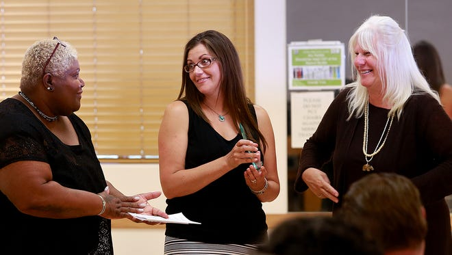 Jeanene Valdes, center, accepts the Community Hero Award from Opal Cole, left, executive director of the Family Crisis Center, and Pam Wiseman, right, executive director of the New Mexico Coalition Against Domestic Violence, during a ceremony on Thursday at the Bonnie Dallas Senior Center in Farmington.
