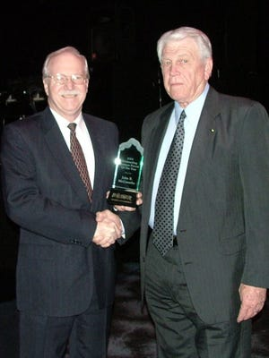Bossier Chamber of Commerce Chairman Jim Waugh presents John McConathy (right) with the 2004 Outstanding Business Person of the Year award in February 2005.