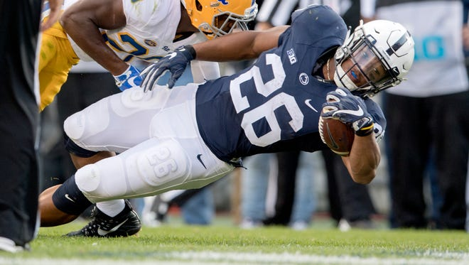 Penn State running back Saquon Barkley (26) dives into the end zone for a touchdown as Pittsburgh's Dennis Briggs defends during an NCAA college football game, Saturday, Sept. 9, 2017 at Beaver Stadium in State College, Pa. Penn State won, 33-14.